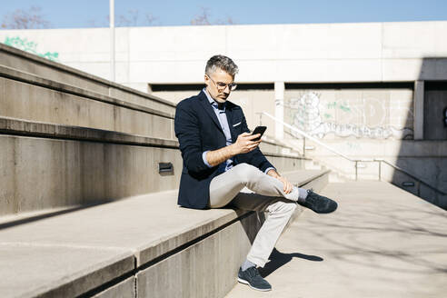 Gray-haired businessman sitting on stairs using cell phone - JRFF04185