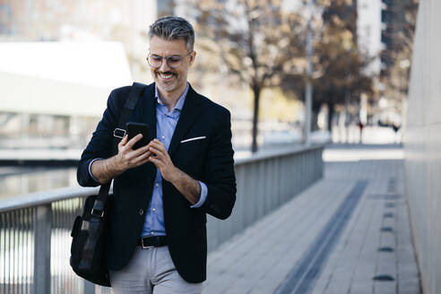 Smiling gray-haired businessman walking in the city using cell phone - JRFF04194