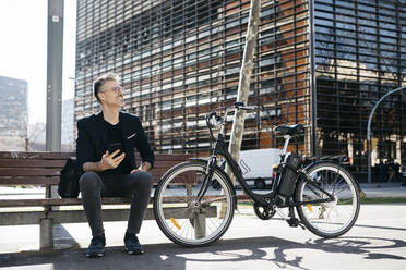 Gray-haired businessman sitting on a bench next to electric bicycle in the city - JRFF04227