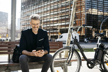 Gray-haired businessman sitting on a bench next to bicycle in the city using cell phone - JRFF04230
