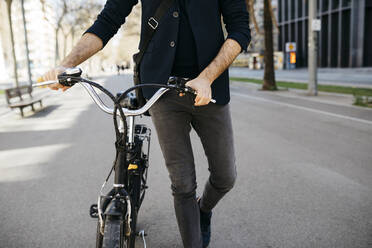 Close-up of businessman pushing a bicycle in the city - JRFF04233