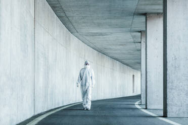 Man wearing protective clothing walking in a tunnel - WVF01510