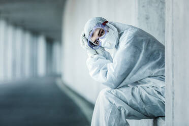 Portrait of a man wearing protective clothing sitting in a niche of a concrete wall in a tunnel - WVF01513