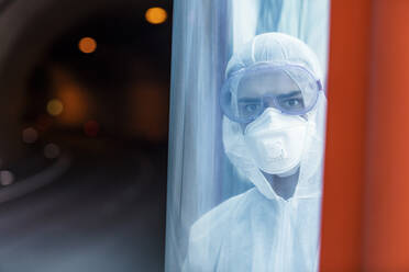 Portrait of man wearing protective clothing behind a glass pane - WVF01516