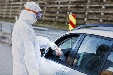 Man wearing protective clothing controlling senior man in car - WVF01519