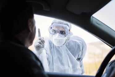 Man wearing protective clothing reprimanding senior man in car - WVF01522