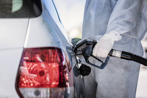 Close-up of man wearing protective clothing refueling car at gas station - WVF01525