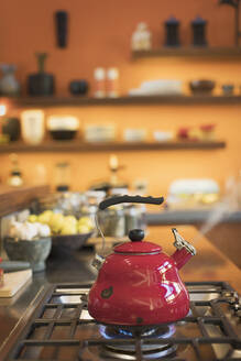 Red tea kettle steaming on stovetop in domestic kitchen - HOXF05221