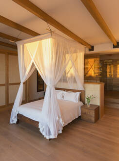White gauze curtains on canopy bed in modern, luxury home showcase interior bedroom - HOXF05239