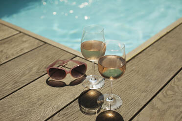 Rose wine glasses and sunglasses at sunny poolside - HOXF05299