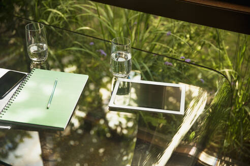 Digital tablet and water glasses on glass table - HOXF05317