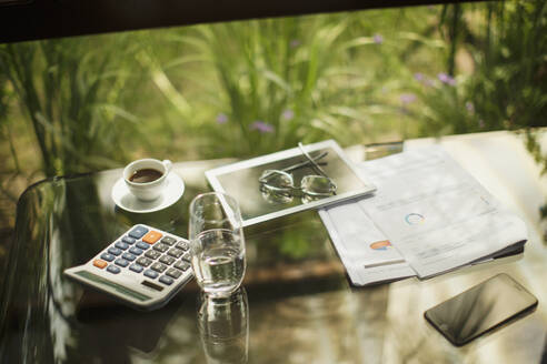 Calculator and digital tablet on table with coffee and paperwork - HOXF05341