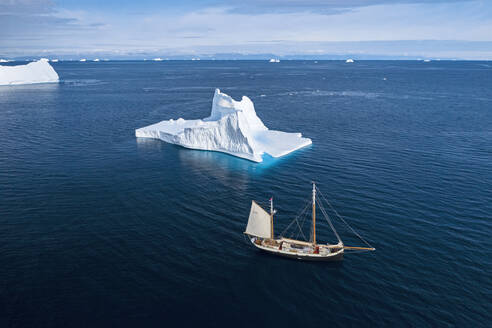 Ship sailing past iceberg on sunny blue Atlantic Ocean Greenland - HOXF05377