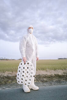 Man wearing protective suit and mask standing on country road with toilet rolls - EYAF00958