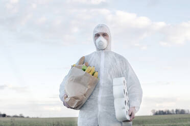 Man wearing protective suit and mask holding toilet rolls and grocery bag in the countryside - EYAF00964