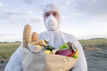 Portrait of man wearing protective suit and mask holding grocery bag in the countryside - EYAF00967
