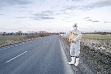 Man wearing protective suit and mask holding grocery bag hitchhiking at a country road - EYAF00973