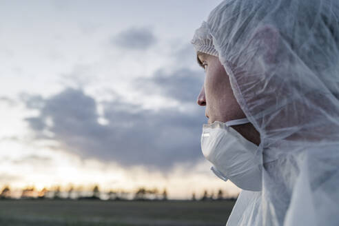 Portrait of man wearing protective suit and mask looking at sunset - EYAF00976