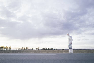 Man wearing protective suit and mask at the roadside of a country road - EYAF00979