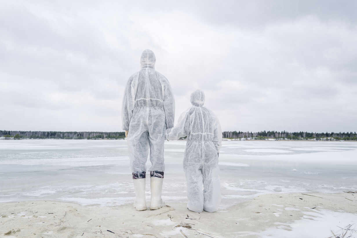 Rear view of father and son wearing protective suits standing at frozen river - EYAF00982 - Ekaterina Yakunina/Westend61