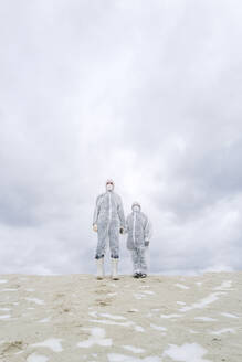 Father and son wearing protective suits standing outdoors in winter - EYAF00988