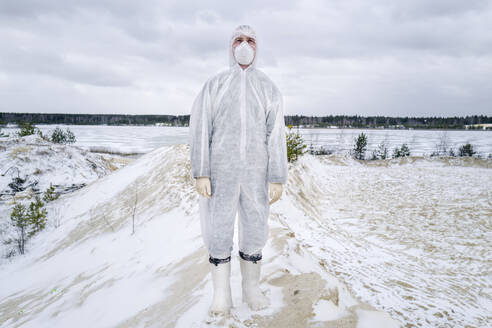 Man wearing protective suit and mask standing in rural winter landscape - EYAF00991