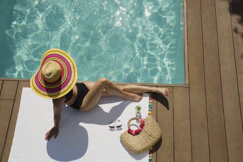 Woman in sun hat sunbathing, relaxing at sunny summer poolside - HOXF05485