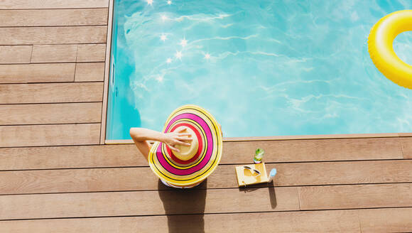 Woman in sun hat relaxing at sunny poolside - HOXF05497