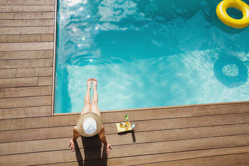 Woman in sun hat relaxing, sunbathing at sunny summer poolside - HOXF05509