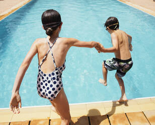 Boy and girl holding hands, jumping into sunny summer swimming pool - HOXF05518