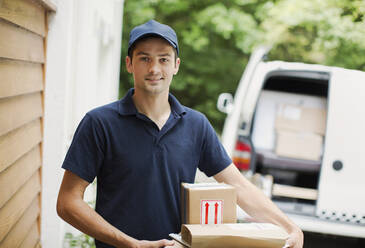 Portrait confident deliveryman with packages at front door - HOXF05524
