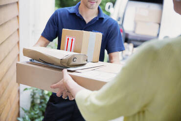 Deliveryman handing packages to woman at front door - HOXF05527