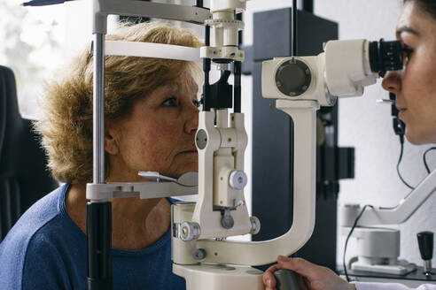 Ophthalmologist examining eyesight of a senior patient - ABZF03024
