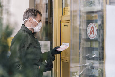 Man with mask waiting in front of pharmacy holding prescription - MFF05127