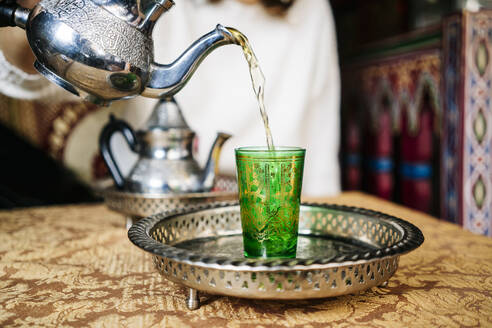 Pouring tea into green glass - DGOF00541