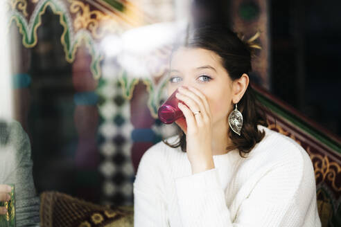 Portrait of young woman drinking tea in a tea shop - DGOF00544