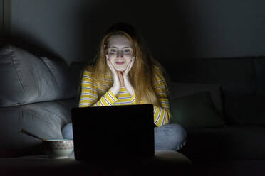 Young woman having a laptop video conference on the couch at home - AFVF05780