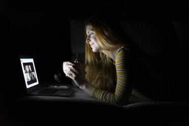 Young woman having a laptop video conference on the couch at home while having dinner - AFVF05792