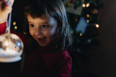 Portrait of excited little girl holding lighted glass ball at Christmas time - GEMF03499