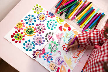 Little girl drawing  ugly viruses with color markers at home - GEMF03504