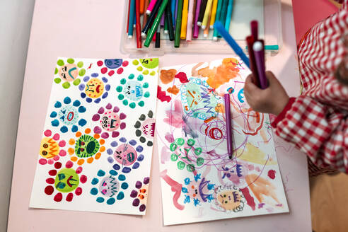 Little girl drawing  ugly viruses with color markers at home - GEMF03507