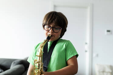 Boy exercising to play the saxophone at home - VABF02678