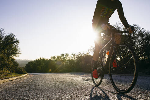 Close-up of athlete riding bicycle on country road at sunset - ABZF03074