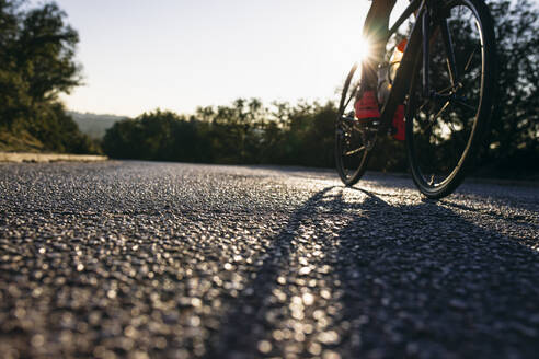 Close-up of athlete riding bicycle on country road at sunset - ABZF03077