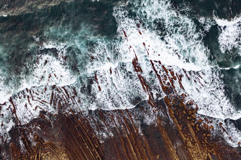 Spain, Biscay, Bilbao, Aerial view of ocean waves brushing against rocky coastline - AMAF00004
