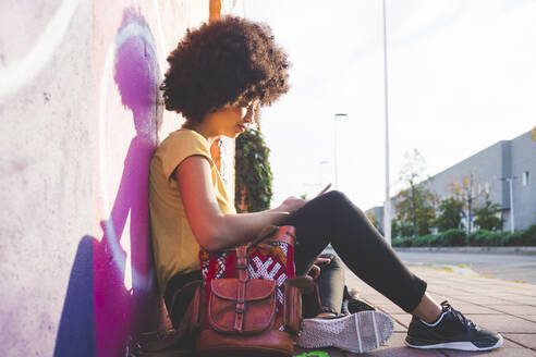 Young woman with afro hairdo sitting at graffiti wall and using smartphone - MEUF00219