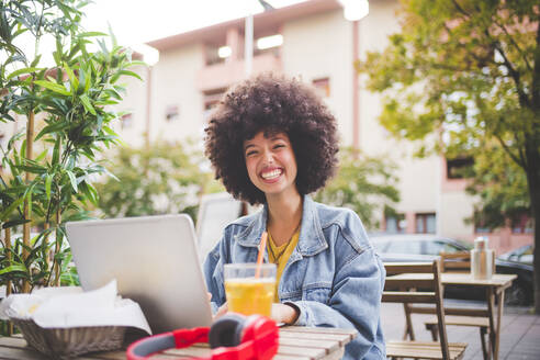 Happy young woman with afro hairdo using laptop at an outdoor cafe in the city - MEUF00252