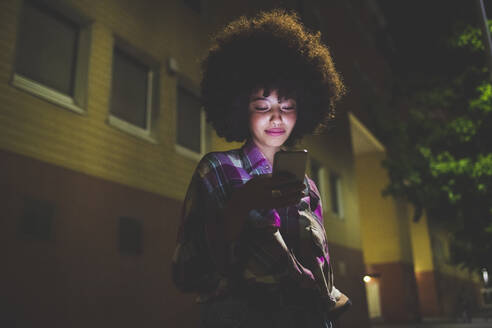 Young woman with afro hairdo using smartphone in the city at night - MEUF00279