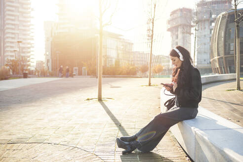 Beautiful woman sitting on a bench and using smartphone, listening to music - MEUF00297