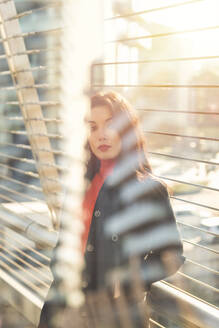 Beautiful woman standing in the sunlight - MEUF00300